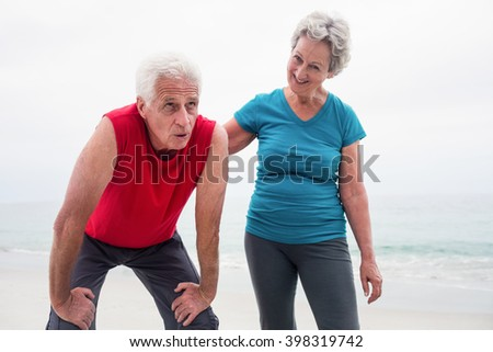 Senior woman comforting a tired senior man on the beach