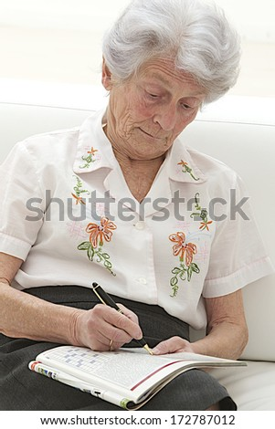 senior woman completing crossword  in a magazine  - stock photo