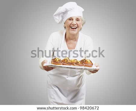 senior woman cook holding a tray with muffins against a grey background - stock photo