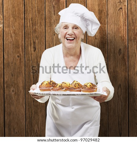 senior woman cook holding a tray with muffins against a wooden background