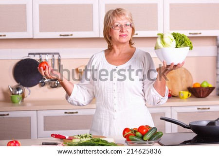 Senior woman cooking in the kitchen. Healthy food - vegetable salad. Diet. Dieting concept. Healthy lifestyle. Cooking at home. Prepare food. woman making salad in kitchen. Beautiful woman at home. - stock photo