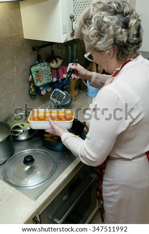 Senior woman cooking orange food on the stove