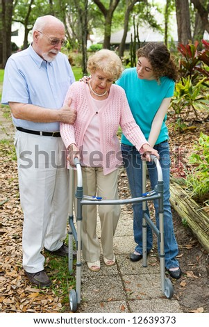 Senior woman depressed about her disability, being comforted by her family. - stock photo