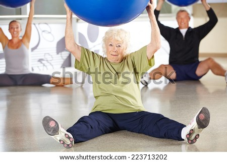 Senior woman doing back traing with gym ball in a fitness center - stock photo
