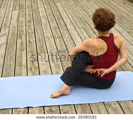 senior woman doing bikram hot yoga on a deck floor - stock photo