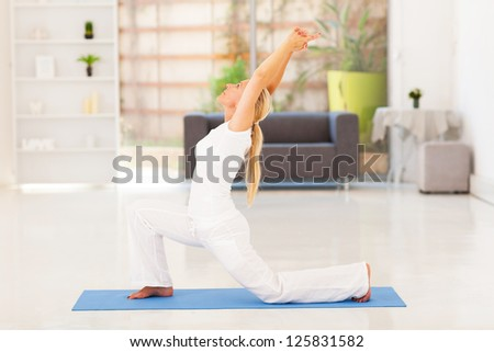 senior woman doing exercise at home - stock photo