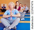 Senior woman doing relaxation exercise in yoga class in a gym - stock photo