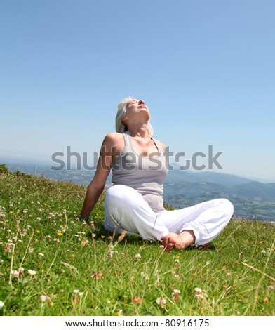 Senior woman doing stretching exercises in countryside - stock photo