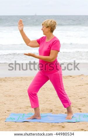 senior woman doing Tai Chi exercise on beach - stock photo