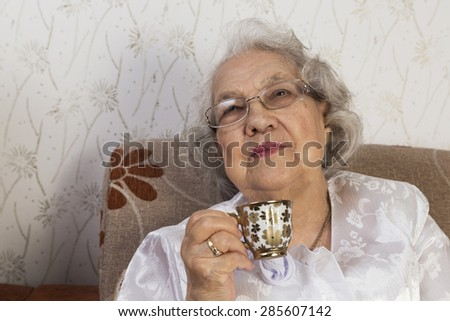 Senior woman drinking coffee - stock photo