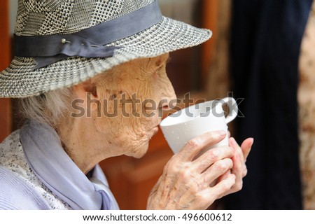 Senior woman drinks a glass of fresh water