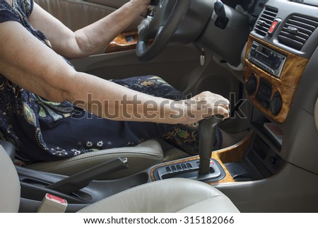Senior woman driving a car - stock photo