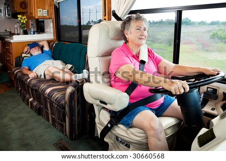 Senior woman driving the motor home on vacation while her husband sleeps in the back. - stock photo