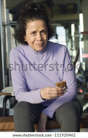 Senior woman eating in gym - stock photo