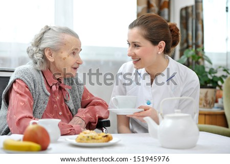 Senior woman eats lunch at retirement home