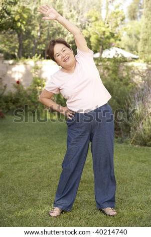 Senior Woman Exercising In Garden - stock photo