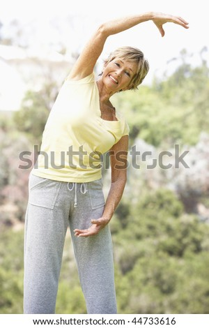 Senior Woman Exercising In Park - stock photo