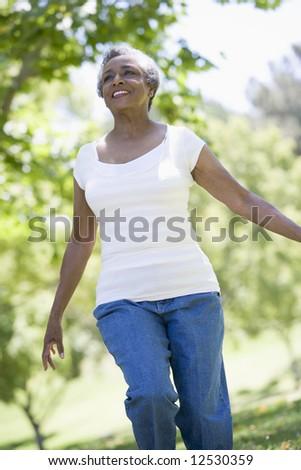 Senior woman exercising outside in park - stock photo