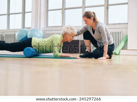 Senior woman exercising with a foam roller being assisted by personal instructor at gym. Physical therapist helping elderly woman in her workout at health club. - stock photo