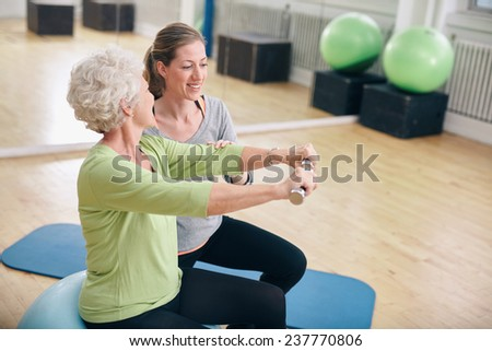 Senior woman exercising with weights in the gym assisted by a young female trainer. Old woman lifting dumbbells with help from personal trainer at rehab. - stock photo