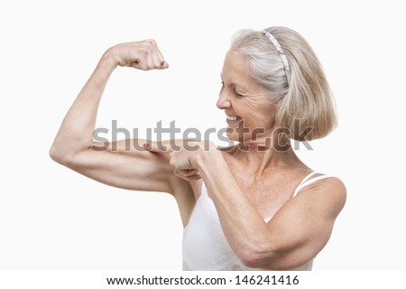 Senior woman flexing muscles against white background - stock photo