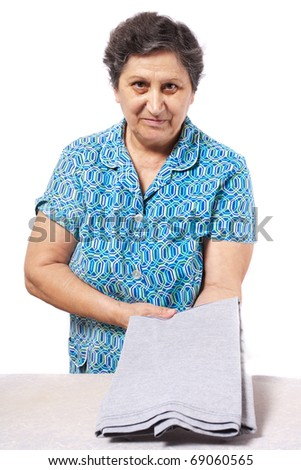 Senior woman folding the clothes, isolated on white background