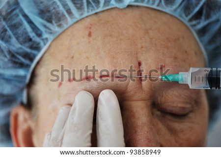Senior woman getting injection at hospital - stock photo