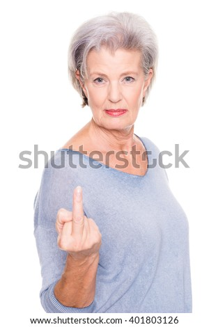 Senior woman gives someone the bird in front of white background - stock photo