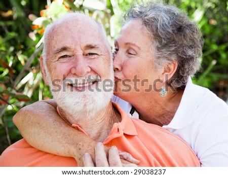 Senior woman giving her husband a kiss on the cheek. - stock photo
