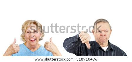 Senior woman giving two thumbs up and grumpy man thumb down - stock photo