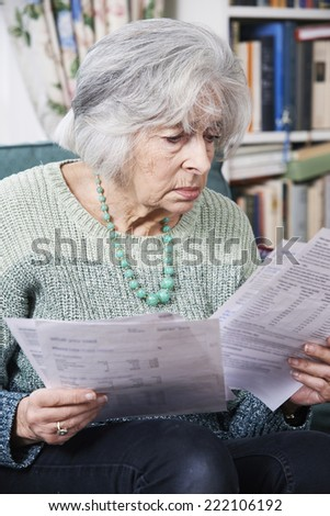 Senior Woman Going Through Bills And Looking Worried - stock photo