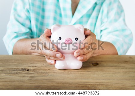Senior woman hand covering piggy bank. front view, metaphoric for hope, saving, retirement, pension and life insurance. - stock photo