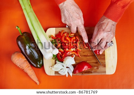 Senior woman hands chopping vegetables on a wooden board in the kitchen - stock photo