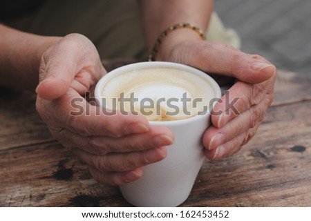 Senior woman hands holding hot cup of coffee - stock photo
