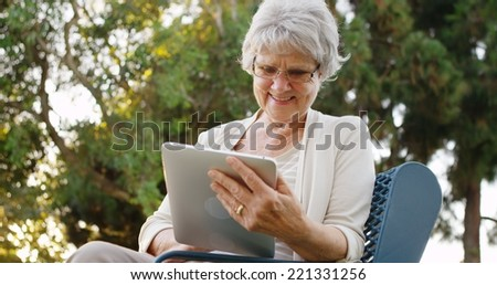 Senior woman happily surfing the web on tablet at the park - stock photo
