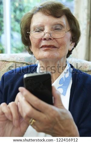 senior woman happily using smart phone - stock photo
