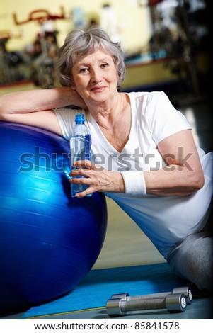 Senior woman having break after exercises - stock photo