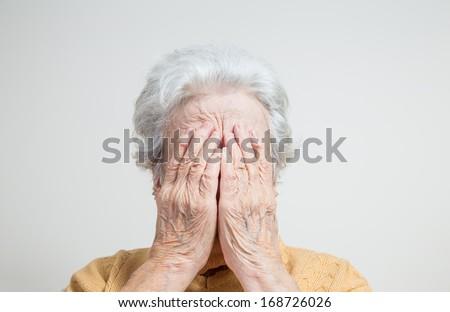 senior woman hiding her face - stock photo
