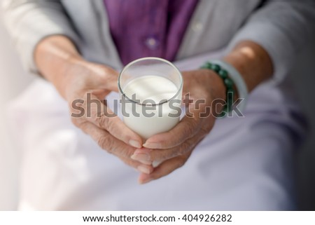 Senior woman holding a glass of milk, health care concept.