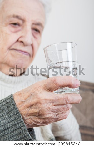 senior woman holding a glass of water - stock photo