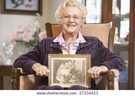 Senior woman holding an old wedding photo - stock photo