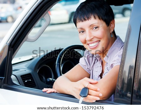 Senior woman holding car key and smiling to you from a  car - stock photo