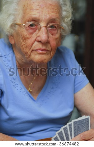 Senior woman holding cards looking at the camera with serious expression