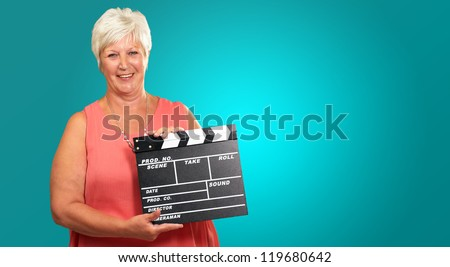 Senior Woman Holding Clapper Isolated On Blue Background - stock photo