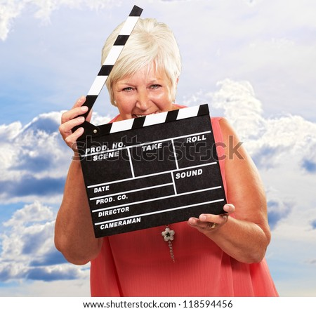 Senior Woman Holding Clapper, Outdoor - stock photo