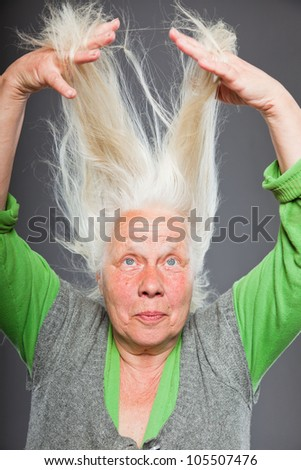 Senior woman holding hands in her hair. Spiritual looking. Studio shot isolated on grey background. - stock photo
