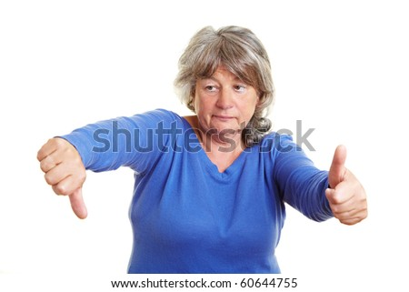 Senior woman holding one thumb up and the other one down - stock photo