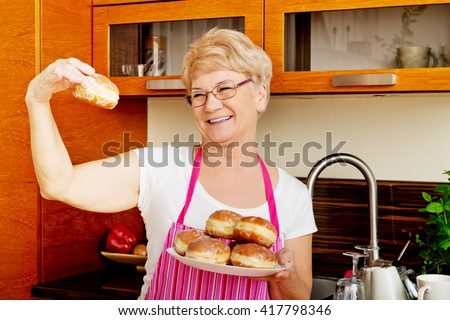 Senior woman holding plate with donuts - stock photo