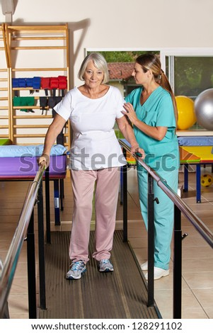 Senior woman holding railing in physiotherapy with a nurse - stock photo