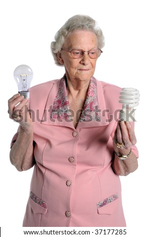 Senior woman holding two kinds of light bulbs - stock photo